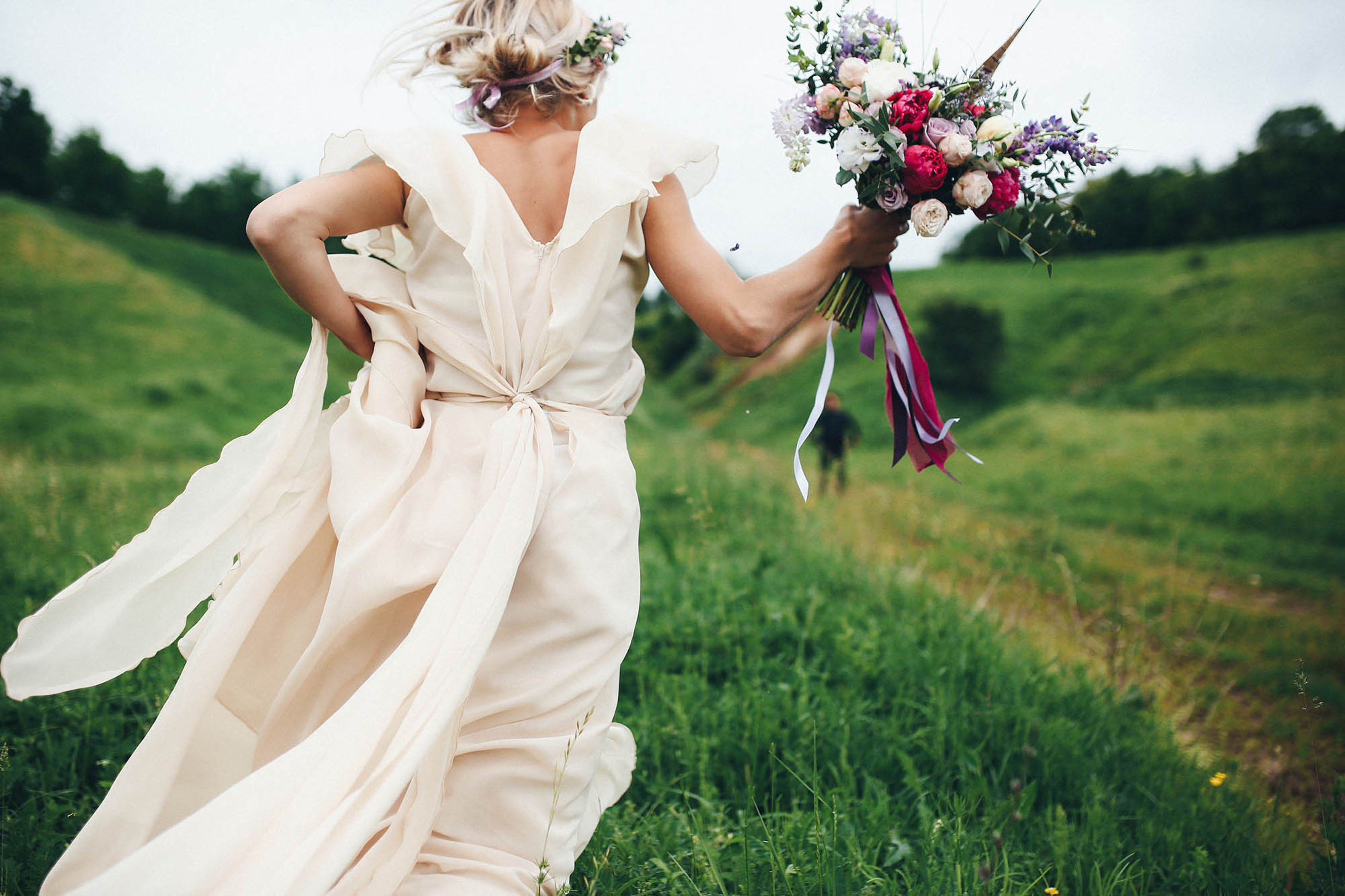 Bride running away from the camera with bouquet in hand